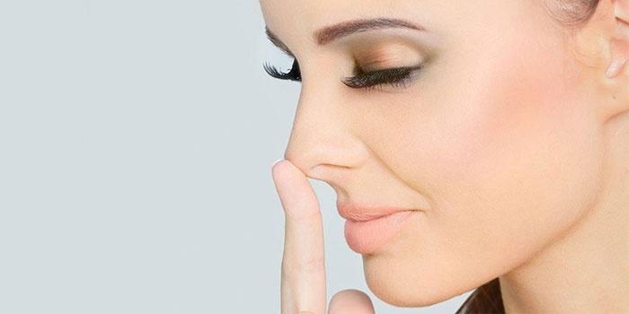 Девушка держится за кончик носа