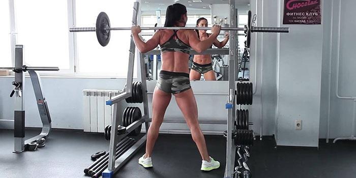 Женщина со штангой в спортзале