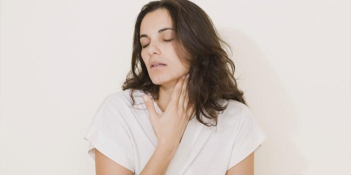 Женщина держится рукой за горло