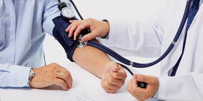Врач измеряет давление пациента