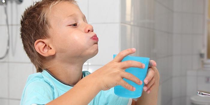 Ребенок полоскает горло содой от ангины