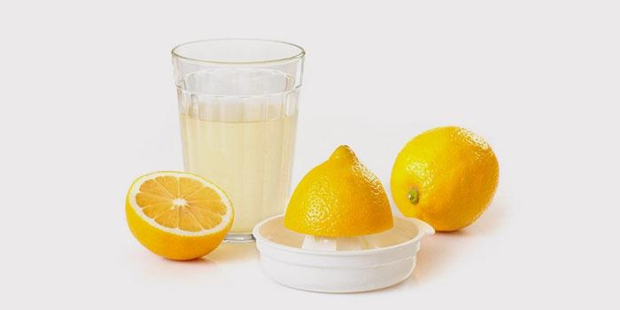 Сок в стакане, лимоны и соковыжималка