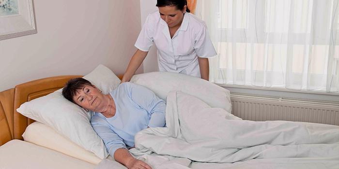 Медсестра ухаживает за лежачей женщиной