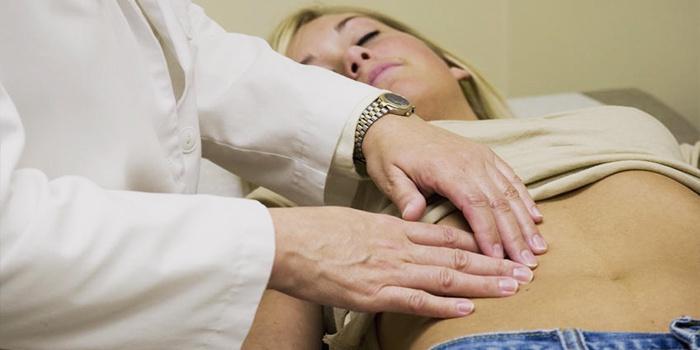 Врач ощупывает живот пациентки