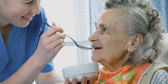 Медсестра кормит женщину после инсульта