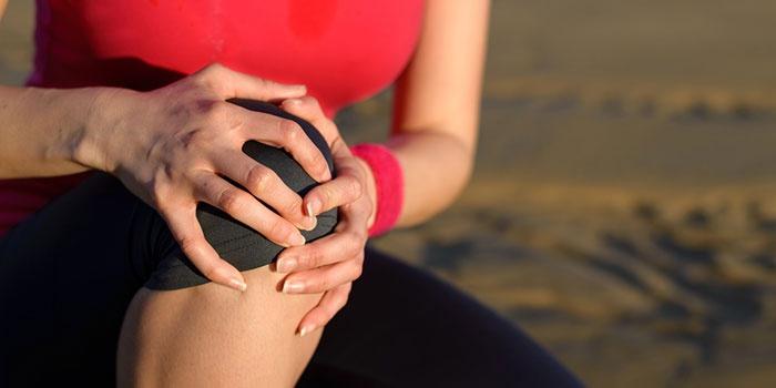 Женщина держит колено руками