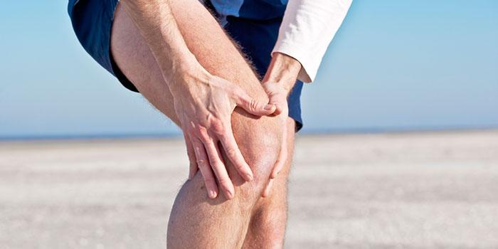 Мужчина держится руками за колено