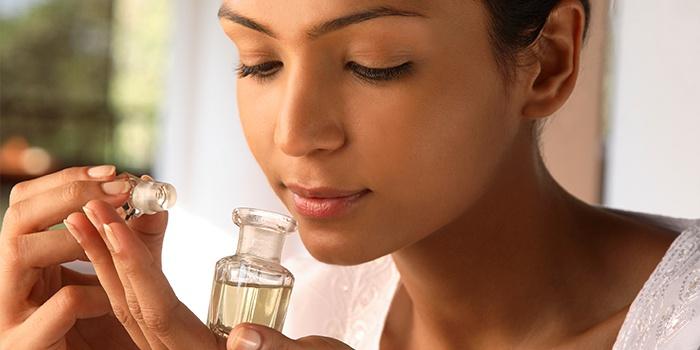 Молодая женщина нюхает масло от головной боли