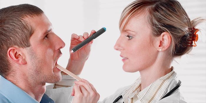 ЛОР проверяет горло у мужчины