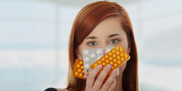 Девушка держит препараты в руке