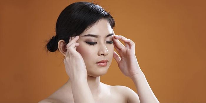 Девушка делает массаж от головной боли