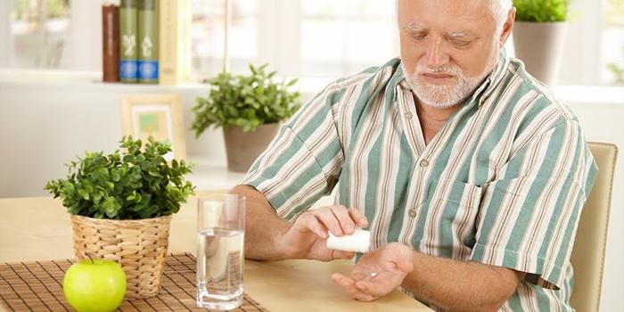 Пожилой мужчина пьет таблетку