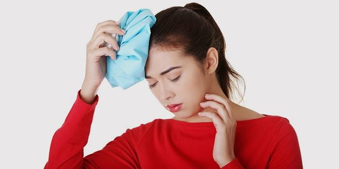 Девушка прикладывает лед от головной боли