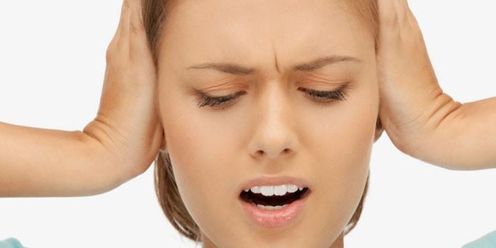 Девушка закрывает уши руками