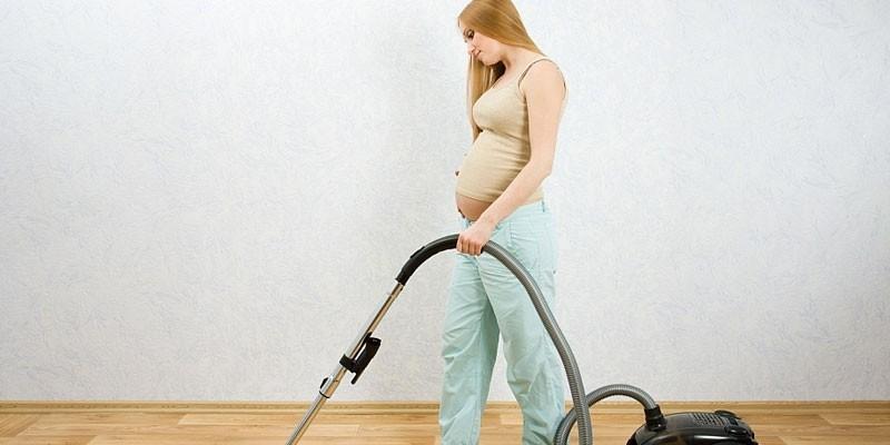 Беременная женщина пылесосит