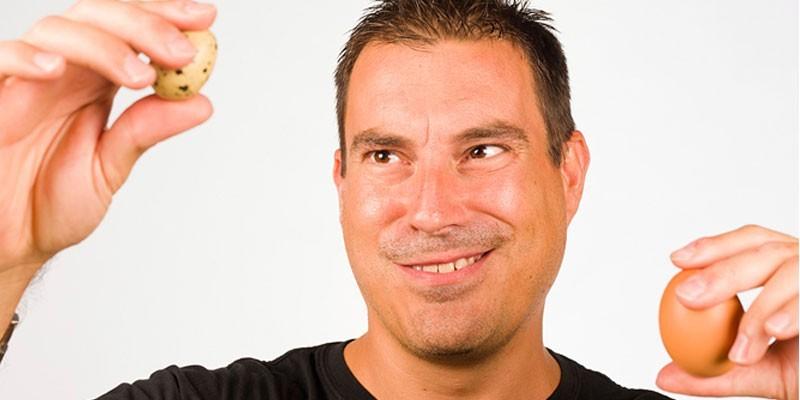 Мужчина держит куриное и перепелиное яйца