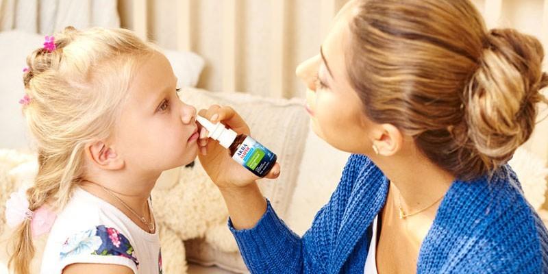 Женщина закапывает нос девочке