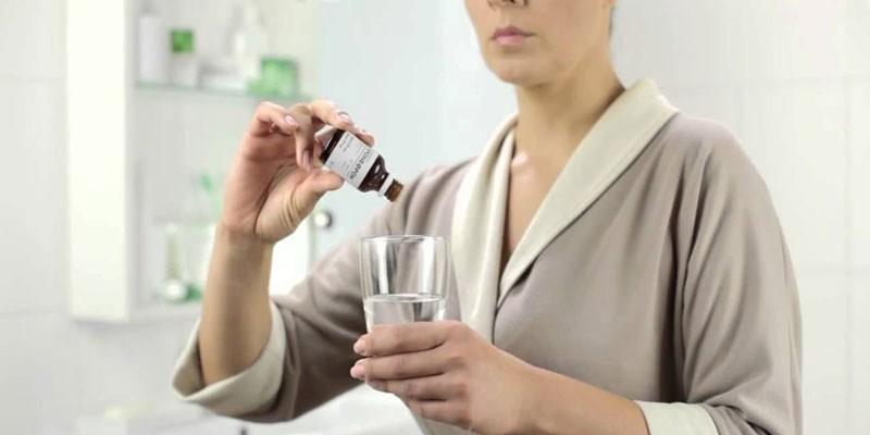 Женщина с каплями и стаканом с водой