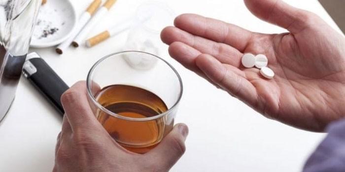 Мужчина с таблетками и стаканом алкоголя
