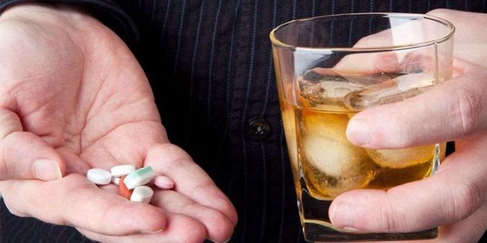 Таблетки и стакан с алкоголем в руках у мужчины