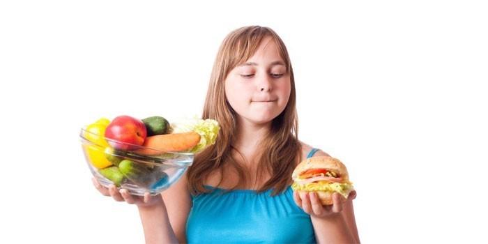 Девочка с овощами, фруктами и гамбургером в руках