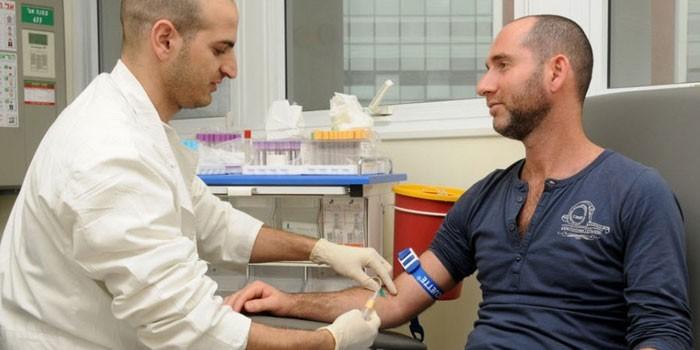 Медик проводит забор крови из вены