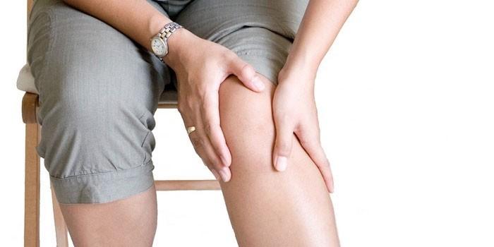 Женщина приложила руки к колену