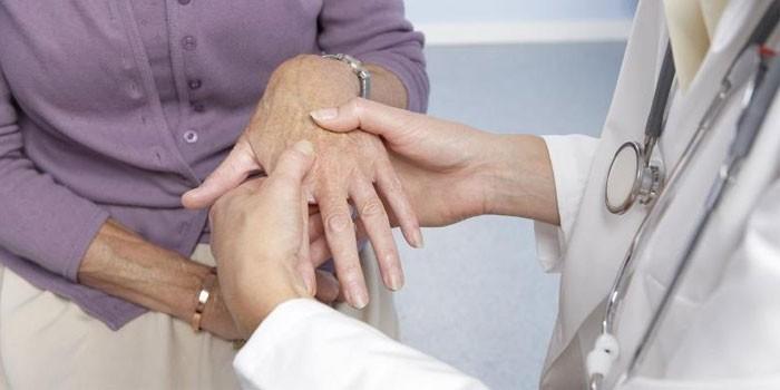 Врач осматривает руку пациентки