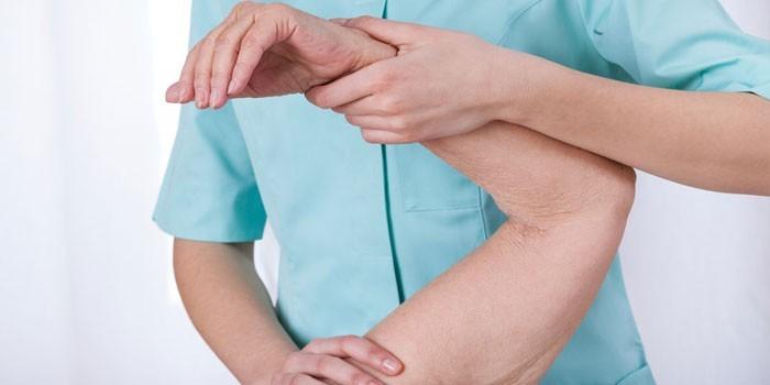 Врач осматривает руку пациента