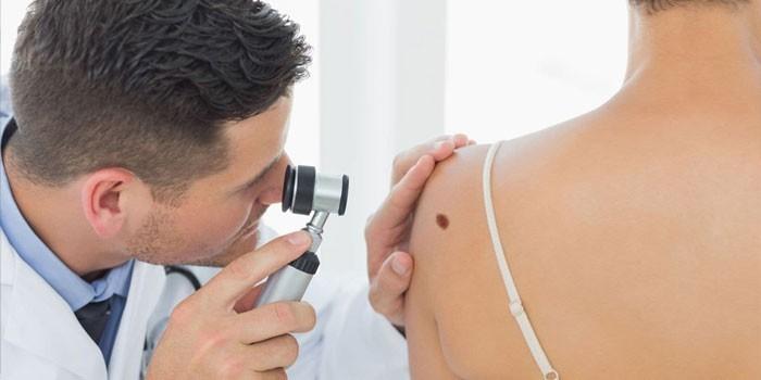 Дермаолог осматривает кожу пациентки