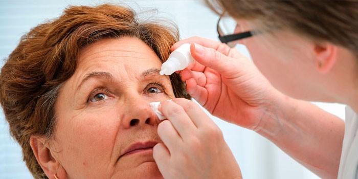 Женщине капают капли в глаза