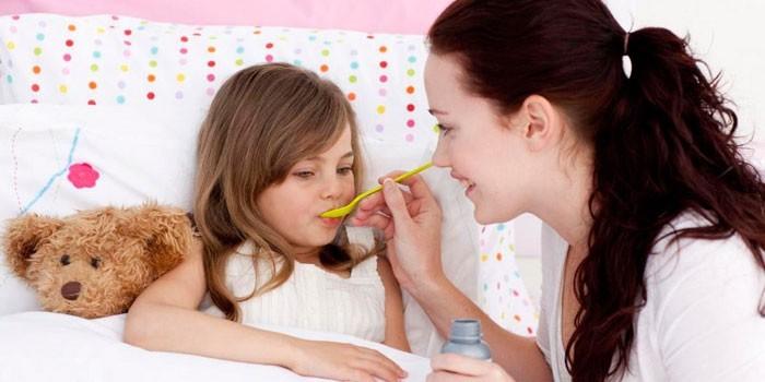 Женщина дает ребенку лекарство