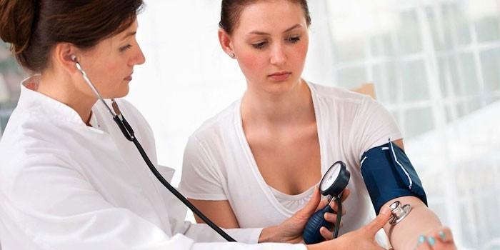 Медик измеряет давление девушке