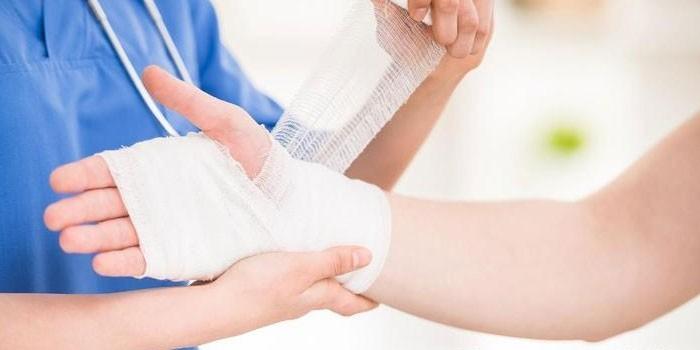 Медик бинтует руку пациента