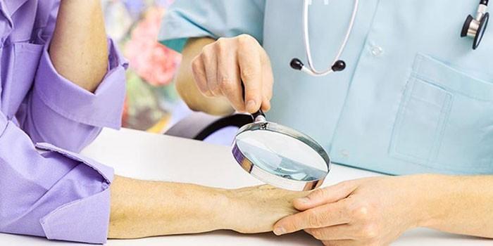 Врач осматривает кожу пациентки