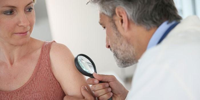 Дерматолог осматривает пациентку