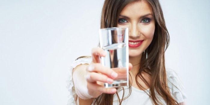 Девушка держит в руках стакан воды