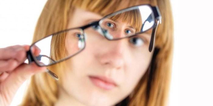 Девушка держит в руке очки