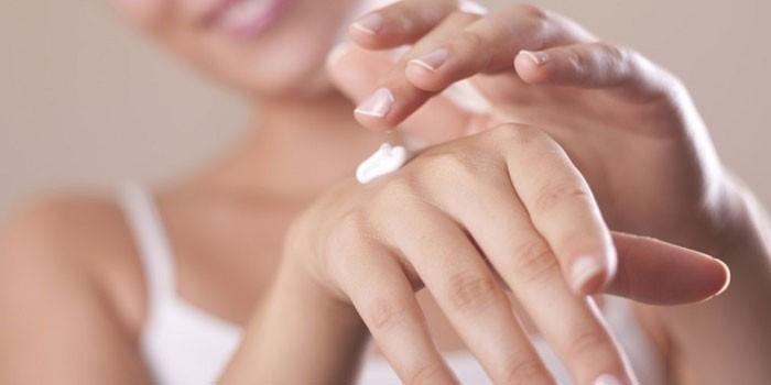 Девушка наносит крем на кожу руки