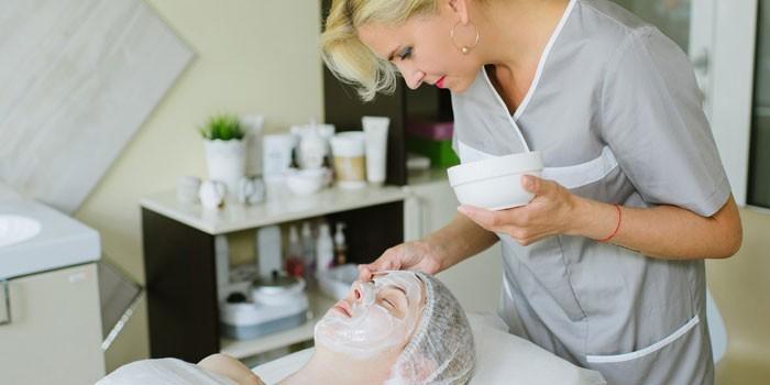 косметолог наносит маску на лицо пациентки