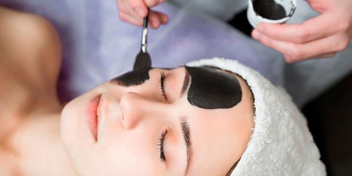 Девушке наносят маску на лицо