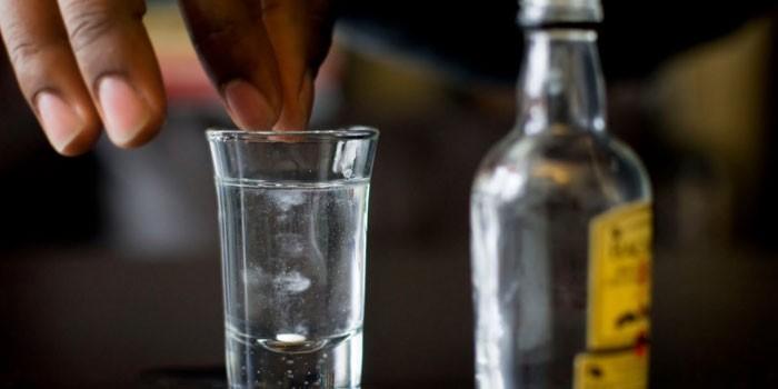 Добавление лекарства в стопку со спиртным