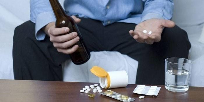 Человек держит в руках бутылку и таблетки
