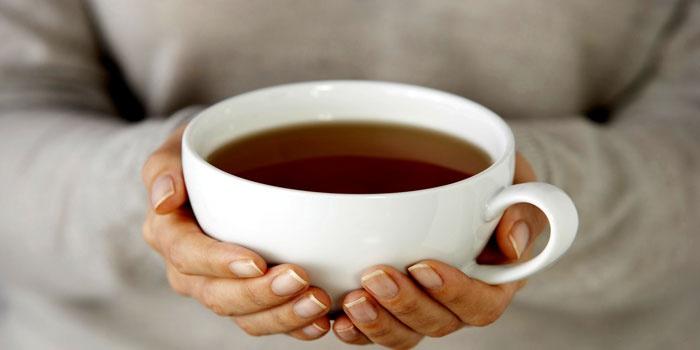 Девушка держит в ладонях чашку с чаем