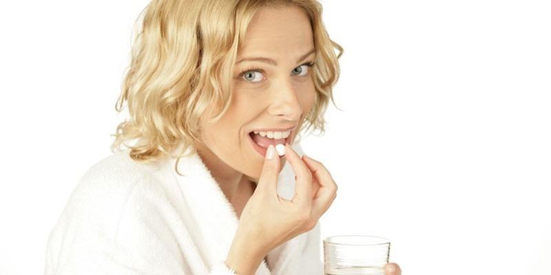 Женщина принимает лекарственный препарат