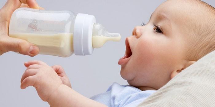 Ребенок и бутылочка со смесью