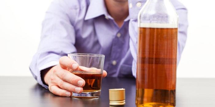 Мужчина со стаканом и бутылкой алкоголя