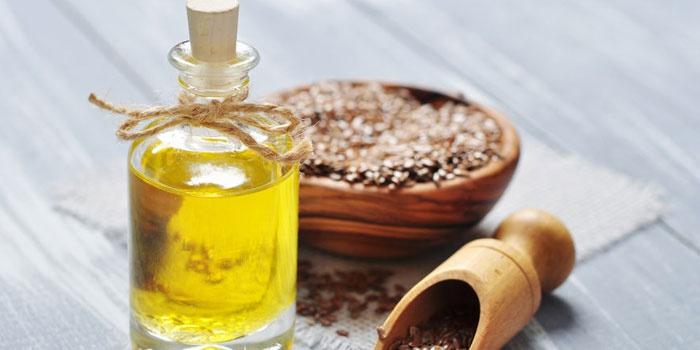Льняное масло в бутылочке и семена льна в тарелочке