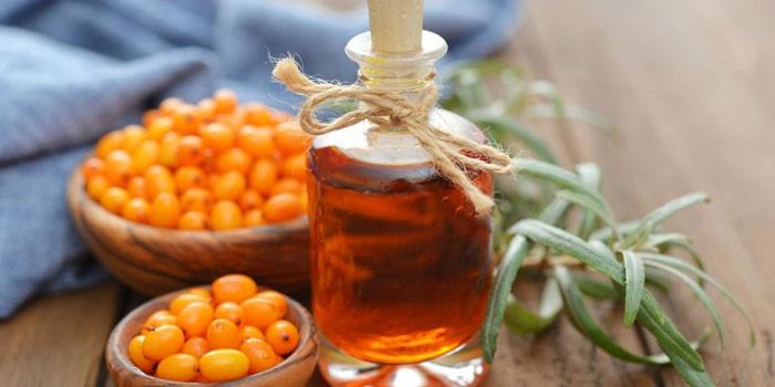 Облепиховое масло в бутылочке, ягоды и листья