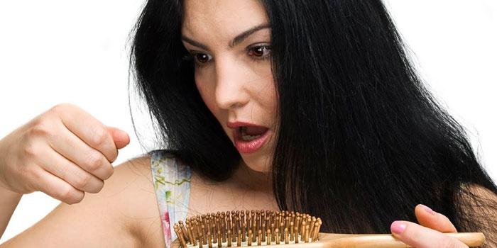 Девушка видит выпавшие волосы на расческе
